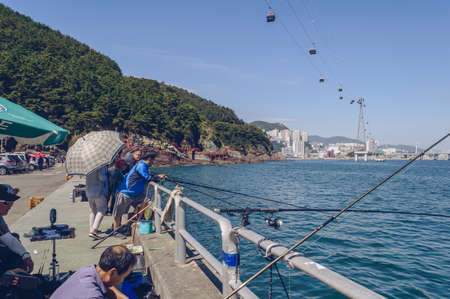 Busan, South Korea, September 14, 2019: mass fishing on sunny day at parking lot of Amnam park with cityscape view