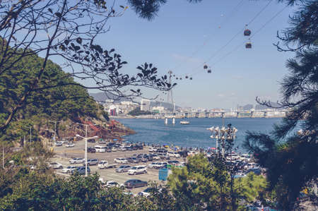 Busan, South Korea, September 14, 2019: parking lot at the sea shore of Amnam park with Songdo cable cars and cityscape view