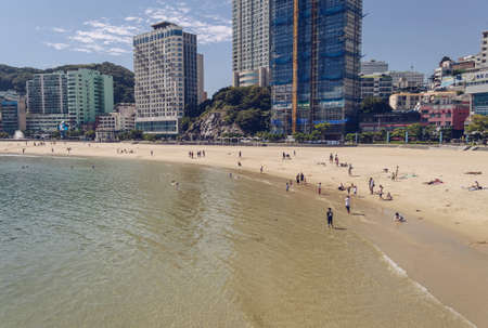 Busan, South Korea, September 14, 2019: beauty of Songdo beach with resting people and cityscape view
