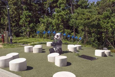 Busan, South Korea, September 14, 2019: sitting area with panda sculpture and blue pinwheels inAmnam park 報道画像