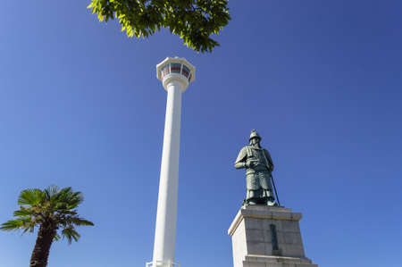 Busan, South Korea, September 14, 2019: view of Busan tower with statue of Yi Sun-sin in front of it and blue skies with trees on background