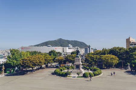 Busan, South Korea, September 14, 2019: view of cityscape from yongdusan park square with admiral Yi Sun-sin statue and people walking 報道画像