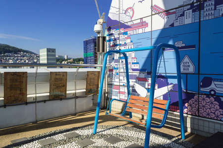 Busan, South Korea, September 14, 2019: photo zone with cute wooden swings decorated with wings and wall with main Busan attractions