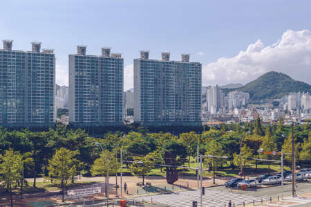 Busan, South Korea September 15, 2019: view from above on part of APEC Naru park and modern cityscape  with hills and blue skies on background Editöryel