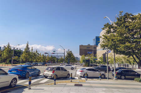 Busan, South Korea September 15, 2019: turning cars and road on sunny day with Shinsegae shopping centre in front