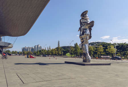 Busan, South Korea September 15, 2019: Side view of modern statue near Busan cinema centre with park and buildings afar