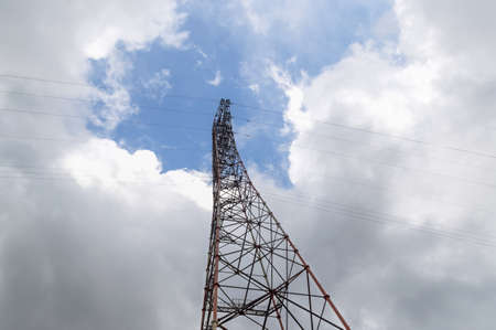 power line support going up into the blue sky with fluffy clouds