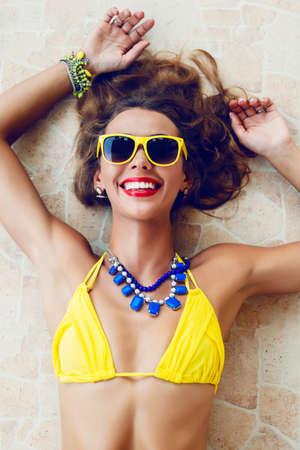 Gelukkig mooie brunette vrouw lachend en met plezier in warme zomerdag, het dragen van stijlvolle neon bikini zonnebril en sieraden Stockfoto