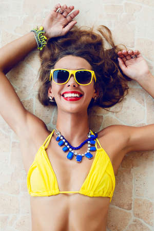 Happy pretty brunette woman smiling and having fun in hot summer day, wearing stylish neon bikini sunglasses and jewelry