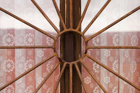 iron curtains: Rusty bars on a window.