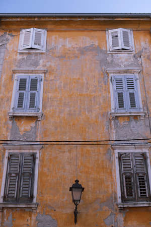weathered: Weathered yellow painted building