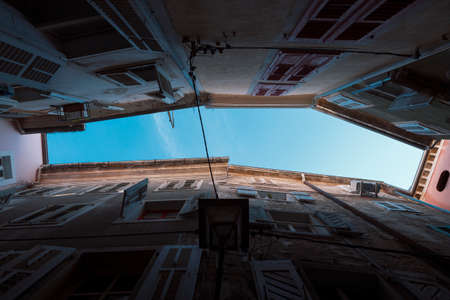 claustrophobic: Looking up in a narrow alleyway