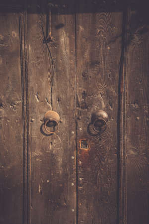 Close up image of vintage wooden door with old metal knockers. Stock Photo