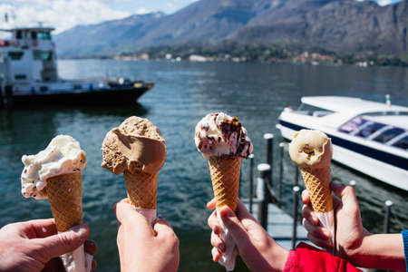 Family hands holding cones of Gelato, Italian ice-cream with blur background of a landscape view of Lake Como in Italy. Concept of family vacation and enjoyment