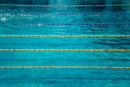 Lanes in a competition  size outdoor swimming pool. Calm Water background. Sense of peace, freedom and forthcoming competition.