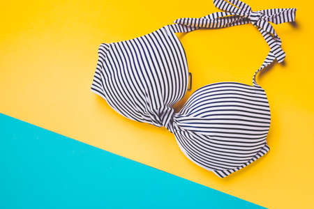 Top view of striped blue and white swimming bra on blue and yellow pastel background. Copy space. Concept of vacation.
