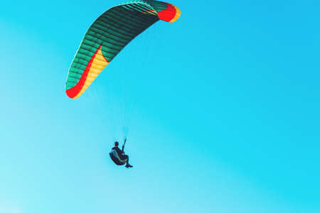 Paraglider flying on colorful parachute in blue clear sky at a bright sunny summer day. Active lifestyle, extreme sport. Adrenaline concept.