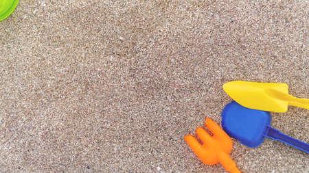 Kinderspielzeug aus Plastik im Sand. Konzept des Familienurlaubs. Ansicht von oben. Platz für Text.