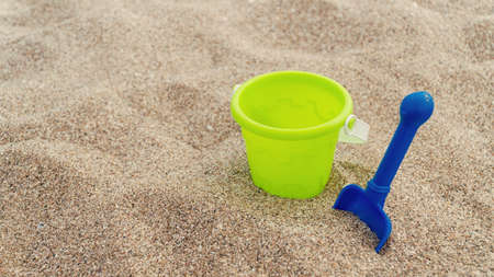 Plastic childrens toys in the sand. Concept of family vacation. Top view. Space for text.