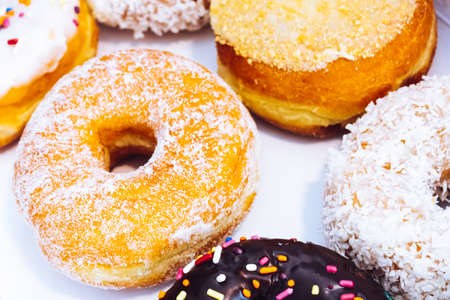 Assorted multicolored donuts in a bakery box with chocolate frosted, glazed and sprinkles donuts. Sugar addiction or festive menu concept.