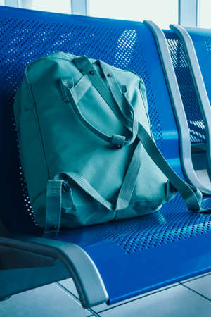 Lounge with seats in the airport, blue tone. Green travel backpack on seat at airport terminal. Delay, Vacantion, Travel concept