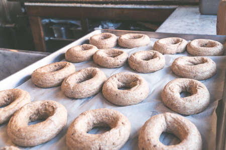American, New York style bagels prepared for baking on baking paper, round bread for breakfast.