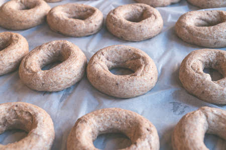 American, New York style bagels prepared for baking on baking paper, round bread for breakfast 写真素材