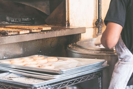 USA, New york: Traditional bagel bakery. Baker in the process of preparing authentic New York style bagels with sesame for baking in the oven 写真素材