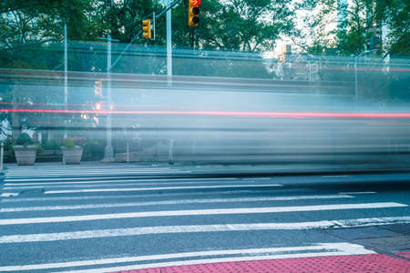 Vehicle light trails on the street of New York. Long exposure in early morning road traffic and pedestrian crossing. Traffic concept