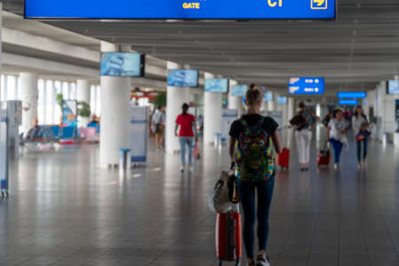 Defocused airport hall with walking travelers in terminal lounge with luggage. Travel concept