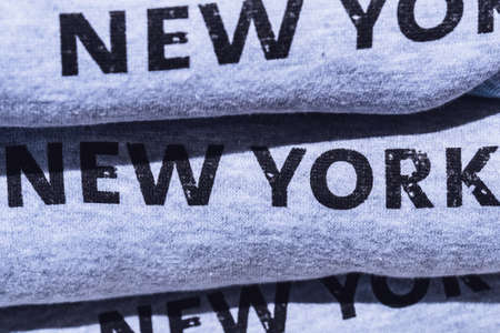 Pile of grey cotton sweatshirts with printed inscription - New York, exposed on tourist shop. Visiting NY conception.