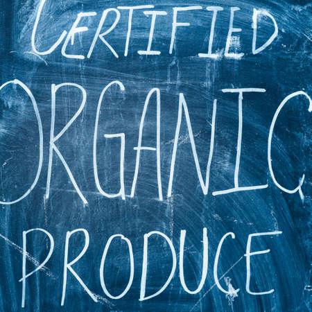 Inscription on a farmers market for certified organic produce written on a blackboard with chalk.