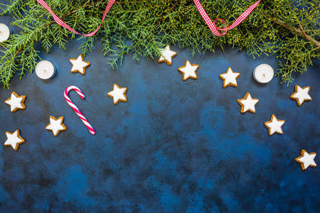 Festive Christmas composition, conifer, candy canes, candles and cookies on bleu vintage background. Christmas, winter, new year concept. Flat lay, top view, copy space for text. 写真素材
