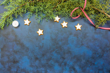 Festive Christmas composition, conifer and cookies on bleu vintage background. Top view, copy space for text.