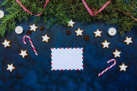 Festive Christmas composition, empty envelope, conifer, candy canes, candles and cookies on bleu vintage background. Christmas, winter, new year concept. Flat lay, top view, copy space for text.