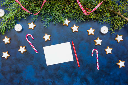 Festive Christmas composition, empty greeting card, conifer, candy canes, candles and cookies on bleu vintage background. Christmas, new year concept. Flat lay, top view, copy space. Winter holidays b 写真素材