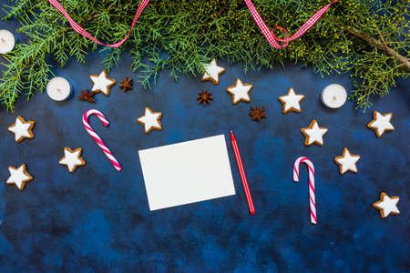 Festive Christmas composition, empty greeting card, conifer, candy canes, candles and cookies on bleu vintage background. Christmas, winter, new year concept. Flat lay, top view, copy space for text.