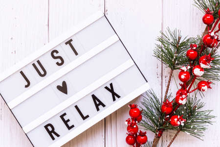 Light box with text Just relax and decorative Christmas evergreen branch and Berries on light rustic wooden background.