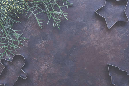 Christmas holiday background with cookie cutters, evergreen fir branch on vintage style dark background. Concept of holiday coziness, top view, flat lay, copy space for text.