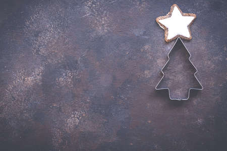 Christmas holiday background with cookie cutters on vintage style dark background. Concept of holiday coziness, top view, flat lay, copy space