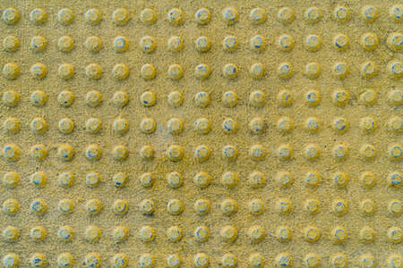 Texture of concrete yellow tiles with round bulges on train station for Blinds Handicap. Yellow braille brick background