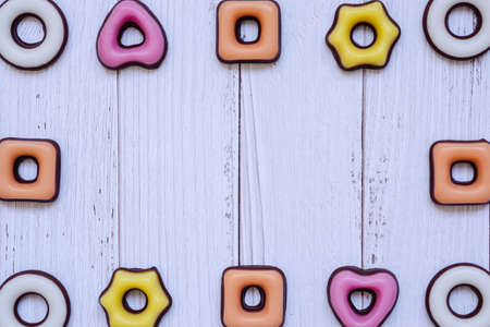 Assorted sweets frame on white wooden background. Top view, copy space for for your greetings.