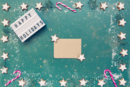 Festive Christmas composition, empty greeting card, conifer, candy canes, cookies and light box with text Happy holiday on green vintage background. Christmas, winter, new year concept. Flat lay, top