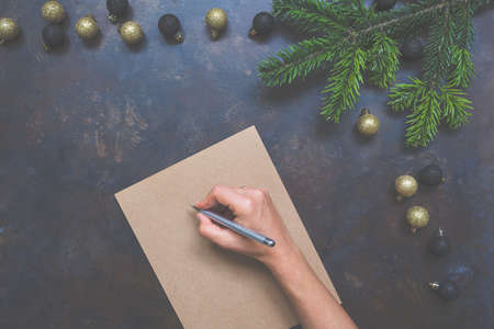 Woman writing Christmas letter or New Year goals on paper on dark vintage background with decorations, top view, copy space. Mock up for to do plans, ideas and hand lettering compositions.