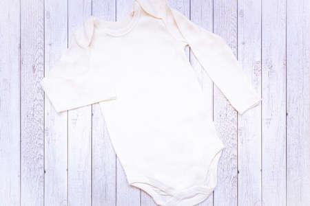 Body neonato bianco unisex in stile neonato con orsacchiotto giocattolo. Mockup piatto.