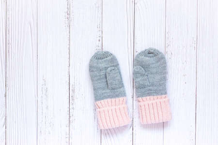 Childrens winter accessories, warm knitted mittens - gray with pink hearts on white wooden background. 写真素材 - 134967512