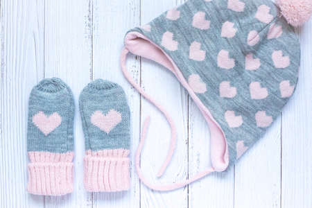 Childrens winter accessories, warm knitted mittens and hat - gray with pink hearts on white wooden background. 写真素材 - 134967515
