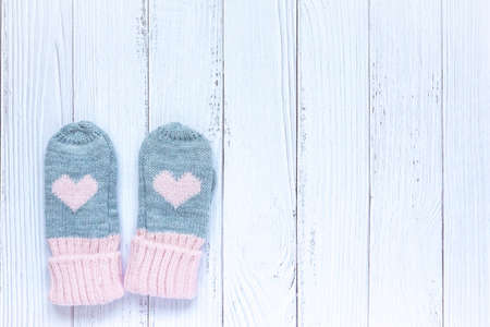 Childrens winter accessories, warm knitted mittens - gray with pink hearts on white wooden background. Flat lay, copy space for text.