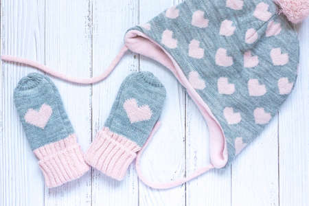Childrens winter accessories, warm knitted mittens and hat - gray with pink hearts on white wooden background.