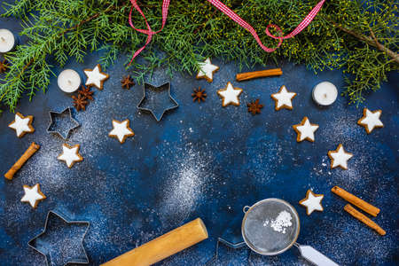 Christmas baking composition with cookies, cookies cutters, flour, spices and green fir branches on blue vintage background, top view, copy space. Winter holiday time concept